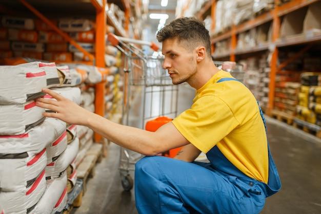 Konstruktor mężczyzna wybiera cement w sklepie z narzędziami. konstruktor w mundurze obejrzyj towary w sklepie dla majsterkowiczów