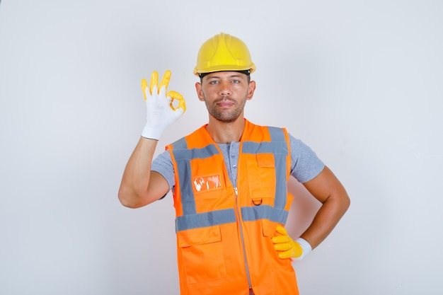 Konstruktor robi ok gest ręką w pasie w mundurze, kasku, rękawiczkach, widok z przodu.