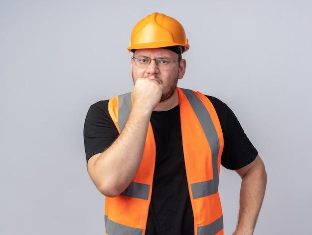 Konstruktor w kamizelce budowlanej i kasku ochronnym, patrząc na aparat zestresowany i nerwowo obgryzający paznokcie stojący nad białymi