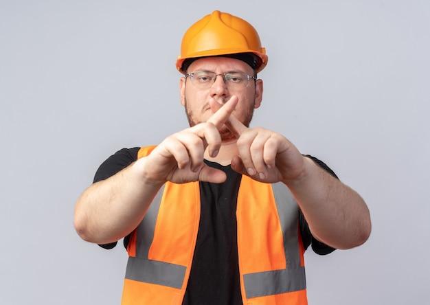 Konstruktor w kamizelce budowlanej i kasku ochronnym, patrząc na kamerę z poważną twarzą, wykonując gest obrony, krzyżujący palce wskazujące stojące na białym tle