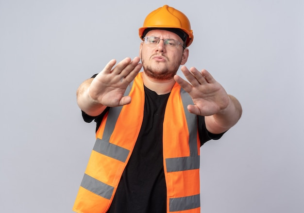 Konstruktor w kamizelce budowlanej i kasku ochronnym, patrząc na kamerę z poważną twarzą, wykonując gest zatrzymania z rękami stojącymi na białym tle