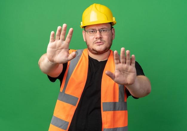 Konstruktor w kamizelce budowlanej i kasku ochronnym, patrząc na kamerę z poważną twarzą, wykonując gest zatrzymania z rękami stojącymi nad zielenią