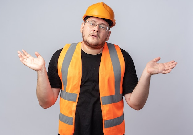 Konstruktor w kamizelce budowlanej i kasku ochronnym, patrząc na kamerę zdezorientowany rozkładając ramiona na boki, nie mając odpowiedzi stojącej na białym tle