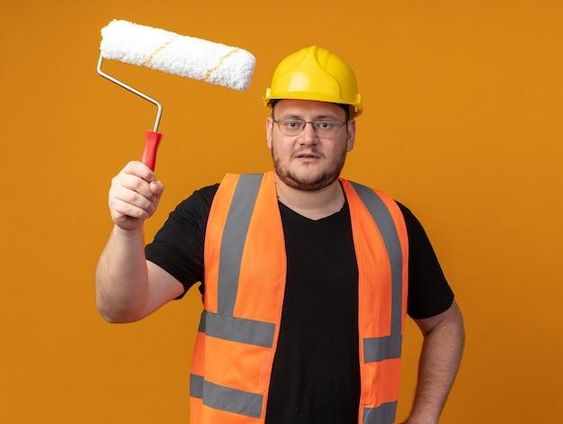 Konstruktor w kamizelce budowlanej i kasku ochronnym, trzymając wałek do malowania, patrząc na kamerę