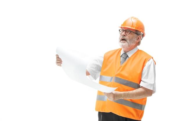 Konstruktor w kamizelce budowlanej i pomarańczowy kask stojący na tle białego studia. specjalista ds. bezpieczeństwa, inżynier, przemysł, architektura, menedżer, zawód, biznesmen, koncepcja pracy