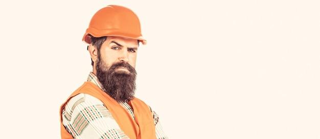 Konstruktor w kasku, brygadzista lub mechanik w kasku. budowniczowie, przemysł. pracownik w mundurze budowlanym. architekt budowniczy. brodaty mężczyzna pracownik z brodą w kasku budowlanym lub kasku