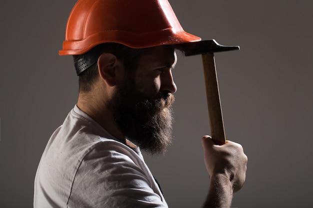 Konstruktor w kasku, młotek, złota rączka, budowniczowie w kasku. brodaty mężczyzna