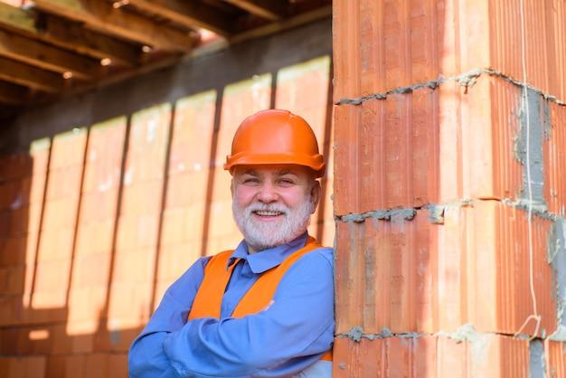 Konstruktor w kasku na zewnątrz technologii budowlanej człowiek w inżynierach kasku budowlanego