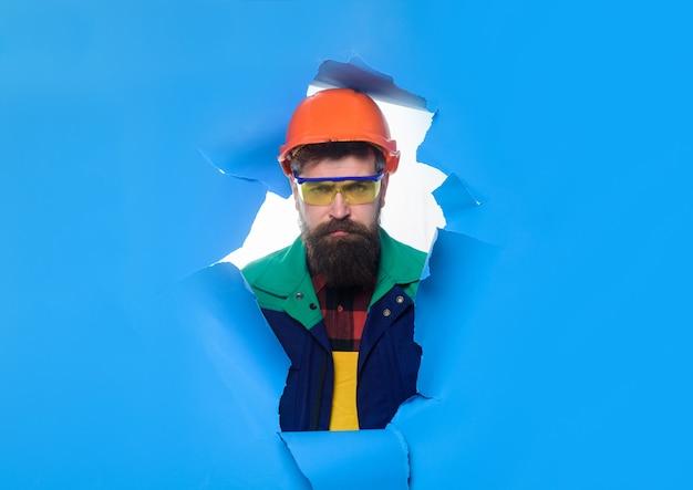 Konstruktor w kasku patrzący przez dziurę w niebieskim papierze budowniczym w kasku ochronnym