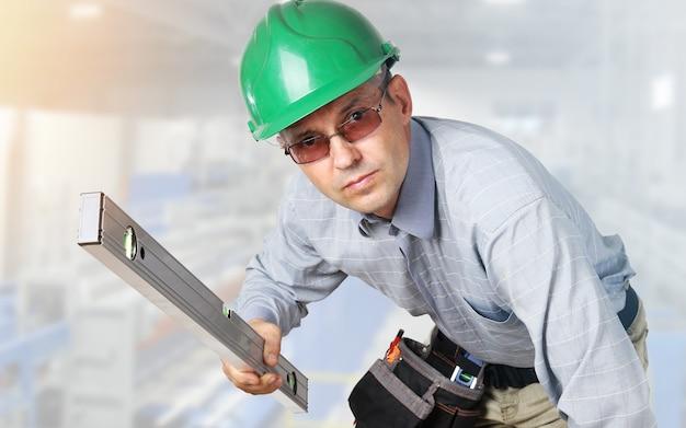 Konstruktor z narzędziami i kaskiem na głowie i poziomicą w rękach zagląda w kamerę