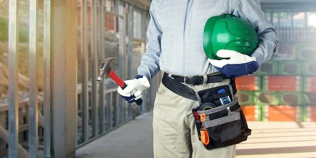 Konstruktor z narzędziami trzyma w dłoniach młotek i kask