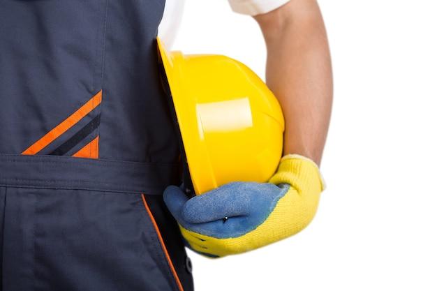 Konstruktor z żółtym kaskiem i rękawiczkami na białym tle