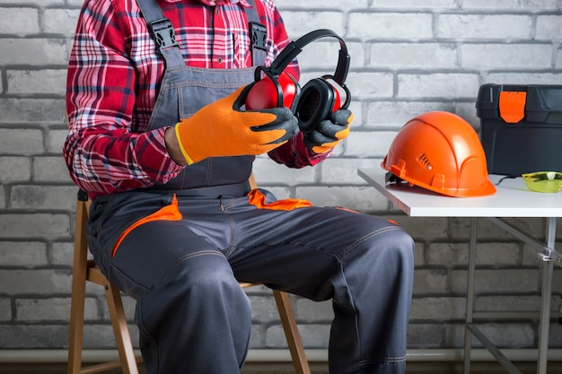 Konstruktor zakłada środki ochrony osobistej. pracownik fizyczny zakładający słuchawki ochronne.
