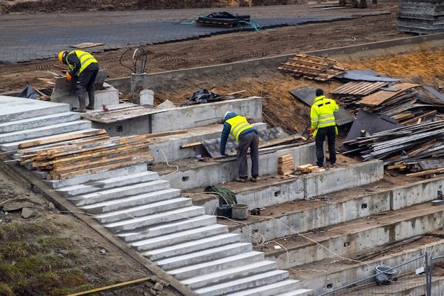 Konstruktorzy pracujący na fundamentach budowlanych na zewnątrz