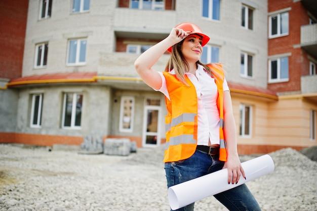 Konstruuje budowniczej kobiety w jednolitej kamizelce i pomarańczowym hełmie ochronnym trzyma biznesowego papier przeciw nowemu budynkowi