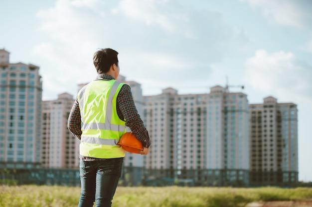Konstruuje mężczyzna pracuje lub sprawdza przy budowa placem budowy