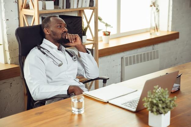 Konsultacja lekarska dla cierpliwego, spokojnego i pogodnego. afroamerykański lekarz podczas pracy z pacjentami, wyjaśniając receptury leków. codzienna ciężka praca na rzecz zdrowia i ratowania życia podczas epidemii.