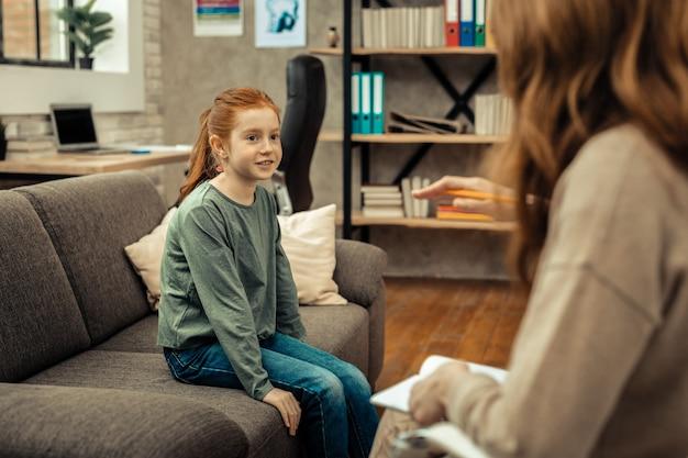 Konsultacja psychologiczna. urocza pozytywna dziewczyna patrząca na swojego terapeutę podczas konsultacji psychologicznej