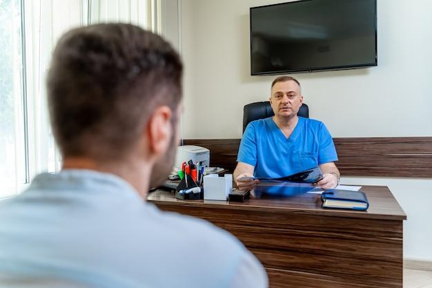 Konsultacja w klinice. lekarz i mężczyzna pacjent siedzi na kanapie w biurze.