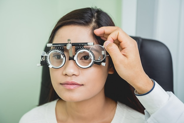 Konsultacja z okulistą. młoda azjatykcia kobieta w kliniki biurze.