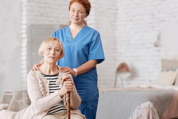 Konsultacje domowe. umiejętnie troskliwa, kompetentna kobieta prowadząca wizytę u bardzo starszej i obawiającej się o zdrowie pani
