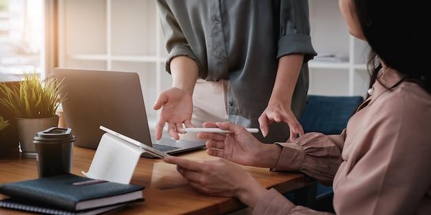 Konsultacje zespołu zarządzających funduszami i dyskusja na temat analizy giełdy inwestycyjnej za pomocą cyfrowego tabletu.