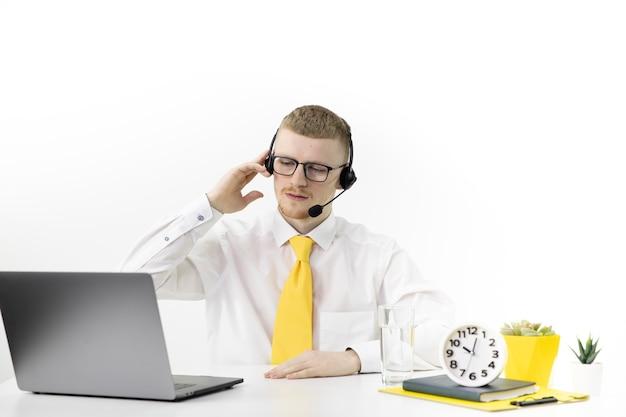 Konsultant online w oficjalnym ubraniu z zestawem słuchawkowym na biurku w biurze call center