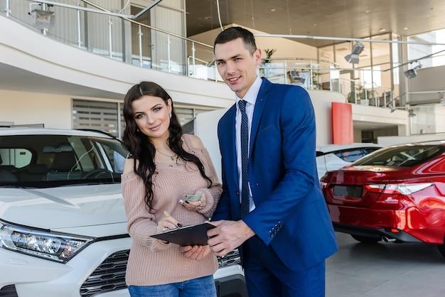 Konsultant podpisuje dokumenty kupującego na samochodzie