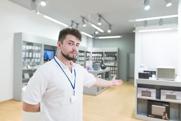 Konsultant stoi w jasnym nowoczesnym sklepie elektronicznym i zaprasza cię ręką