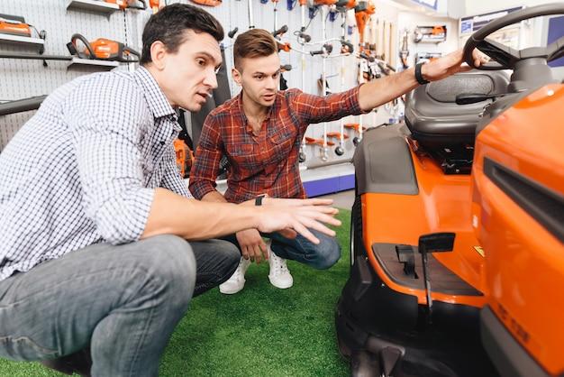 Konsultant w sklepie z narzędziami ogrodniczymi pokazuje kosiarkę do trawy klienta.
