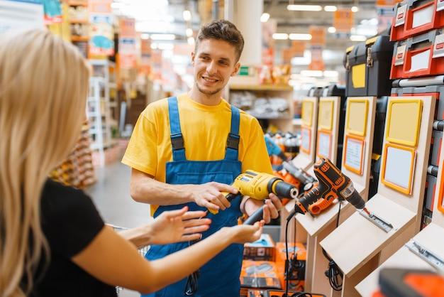 Konsultantka i konsumentka w sklepie z narzędziami. sprzedawca w mundurze i kobieta w sklepie dla majsterkowiczów, zakupy w supermarkecie budowlanym