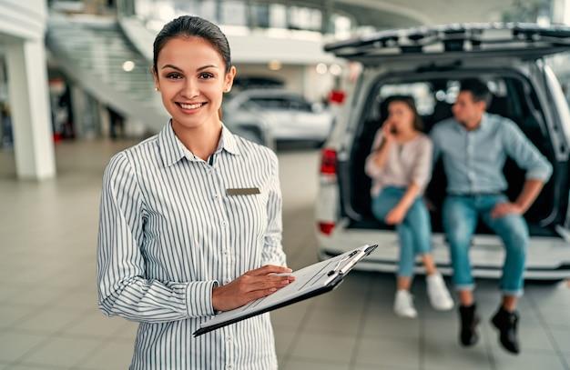 Konsultantka młodej sprzedawczyni w salonie samochodowym. w tle para siedzi w otwartym bagażniku swojego nowego samochodu.