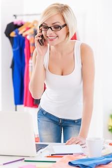Konsultantka mody w pracy. wesoła młoda kobieta rozmawia przez telefon komórkowy i patrzy na laptopa