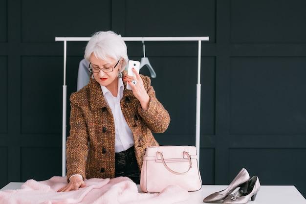Konsultantka mody w salonie. starszy modna kobieta. osobisty stylista w pracy