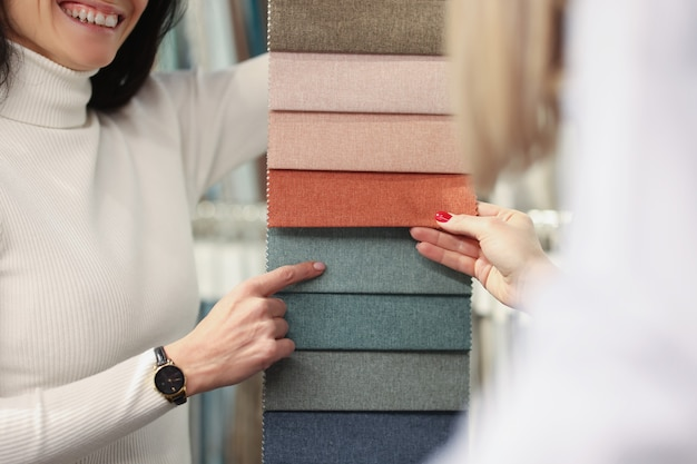 Konsultantka pokazuje kupującemu różne tkaniny do wyboru z wyboru materiału