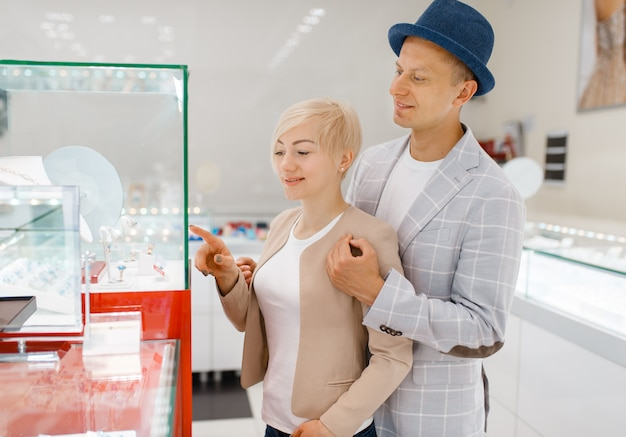 Konsumenci płci męskiej i żeńskiej patrząc na biżuterię w sklepie jubilerskim. mężczyzna i kobieta wybiera obrączki ślubne. przyszła panna młoda i pan młody w sklepie jubilerskim. miłość para kupuje złotą dekorację