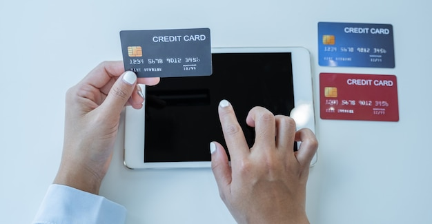 Konsumenta kobieta ręka trzyma makiety karty kredytowej, gotowe do wydatków zapłacić finanse online zakupy według produktów rabatowych za pośrednictwem tabletu z domowego biura.