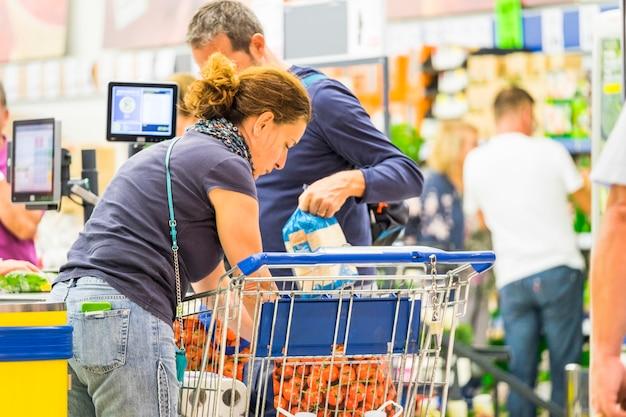 Konsumpcjonizm realna rodzina żonaty mężczyzna i kobieta kaukascy ludzie kupujący jedzenie i napoje, aby mieszkać w domu