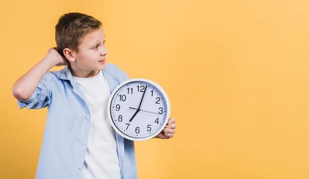 Kontemplacyjna chłopiec trzyma bielu zegar w ręce patrzeje daleko od