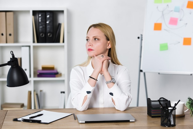 Kontemplacyjny blondynki bizneswomanu młody obsiadanie przy miejscem pracy w biurze