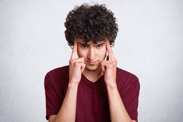 Kontemplacyjny przystojny nastolatek z kręconymi włosami trzyma oba palce wskazujące na skroniach