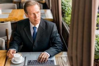 Kontemplowany biznesmen patrząc przez szklane okno z filiżanką kawy i laptopa na biurku