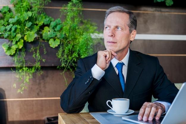 Kontemplowany biznesmen siedzi w caf� z filiżanką kawy i laptopa na biurku