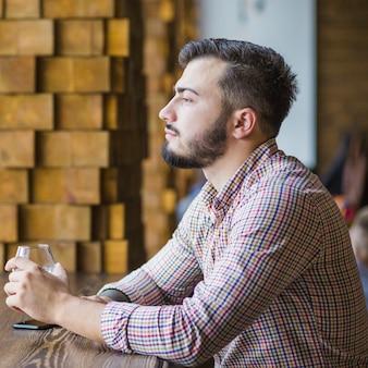 Kontemplowany młody człowiek trzyma kieliszek