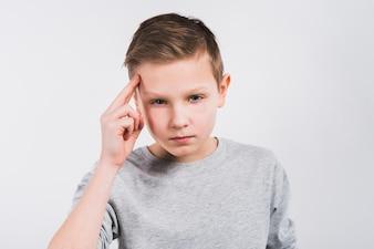 Kontemplująca chłopiec patrzeje kamery pozycja przeciw popielatemu tłu