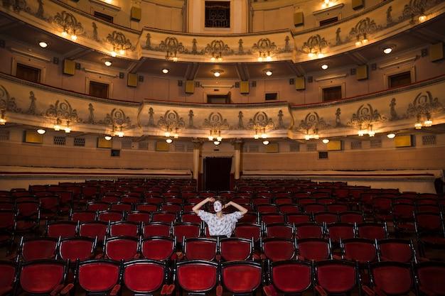Kontemplujący żeński mima artysta siedzi samotnie w audytorium