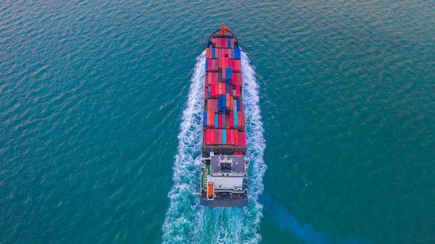 Kontenerowiec przewożący pojemnik do importu i eksportu firm logistycznych i transportowych kontenerowcem na otwartym morzu, widok z lotu ptaka.