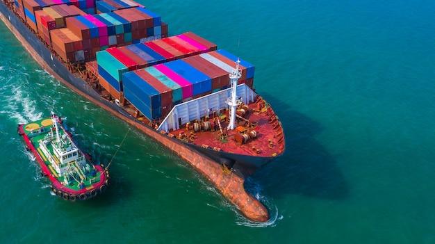 Kontenerowiec przybywający do portu, holownik i kontenerowiec płynący do portu morskiego, logistyczny import eksportowy i transport, widok z lotu ptaka.