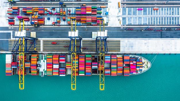 Kontenerowiec przybywający do portu, załadunek kontenerowca w porcie morskim, logistyczny import handlowy eksport i transport, widok z lotu ptaka.