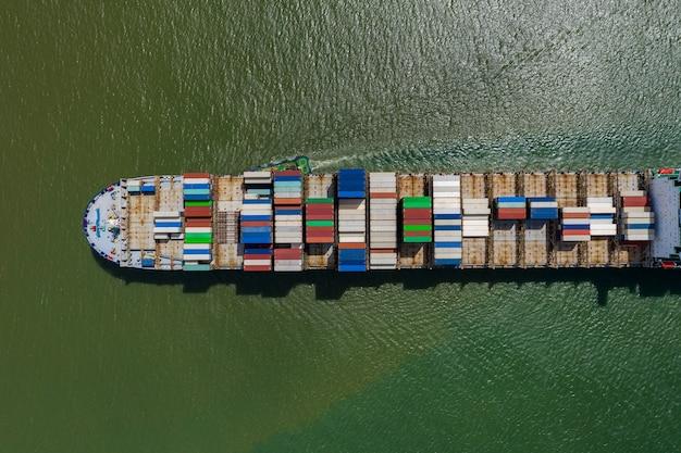 Kontenerowiec w eksporcie i imporcie oraz logistyce. wysyłka ładunków drogą morską. transport wodny międzynarodowy. koncepcja widok z lotu ptaka z góry z drona